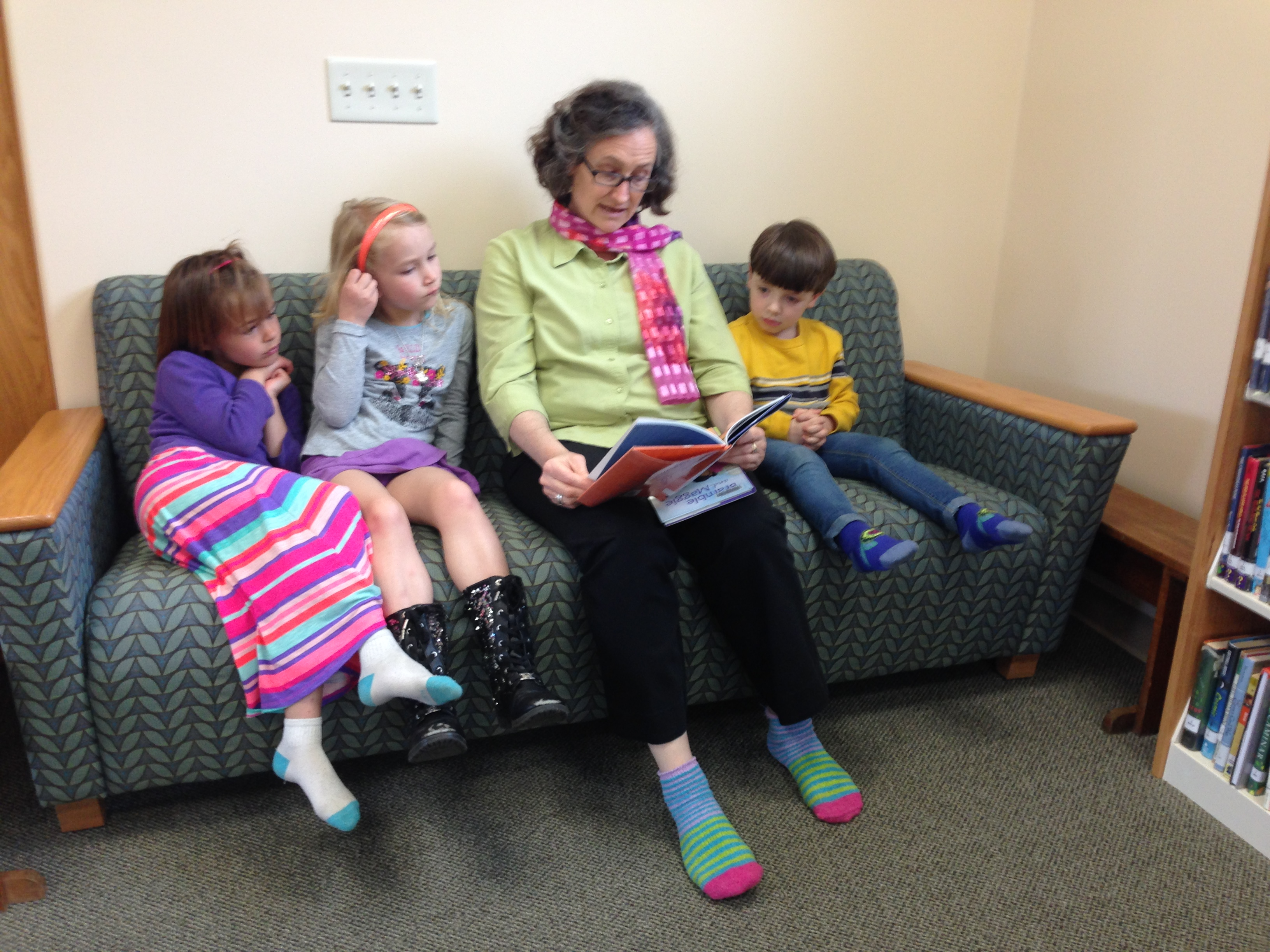 Liz Jacobson and young patrons read a story